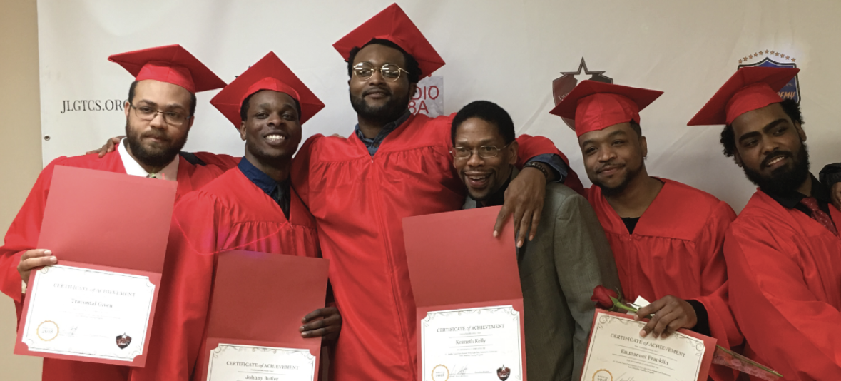 Six graduates posing with their diplomas.